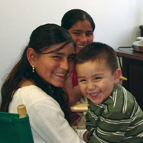 Two young girls and one toddler boy sibling smiling in an office