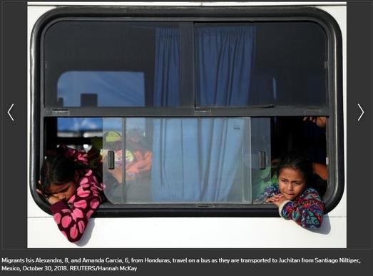 Two Honduran girls leaning out of window of bus as they are transported through Mexico
