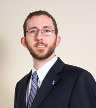 Chest up of a man with shirt brown hair, short brown beard and glasses, wearing a dark blue suit with white shirt and light blue striped tie