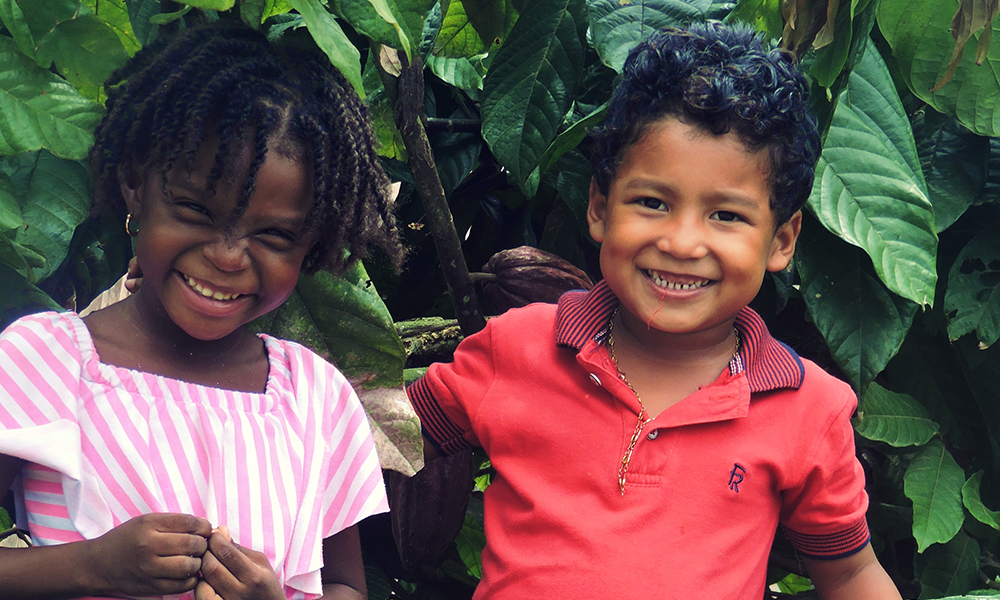 Young boy and young girl smiling in front of big green leaves