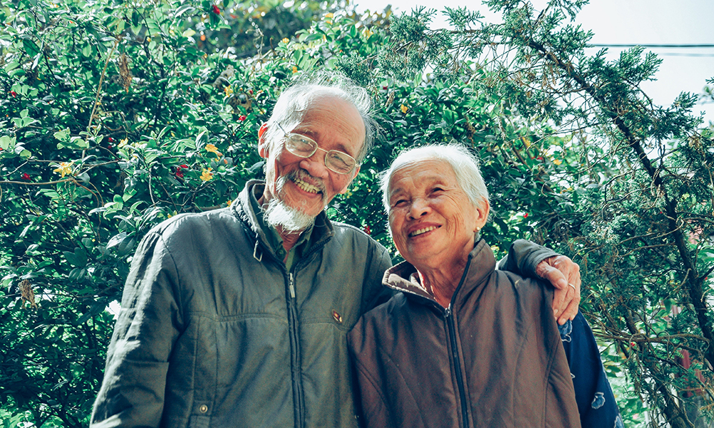 Older smiling Asian couple standing with arms around each other in front of green trees