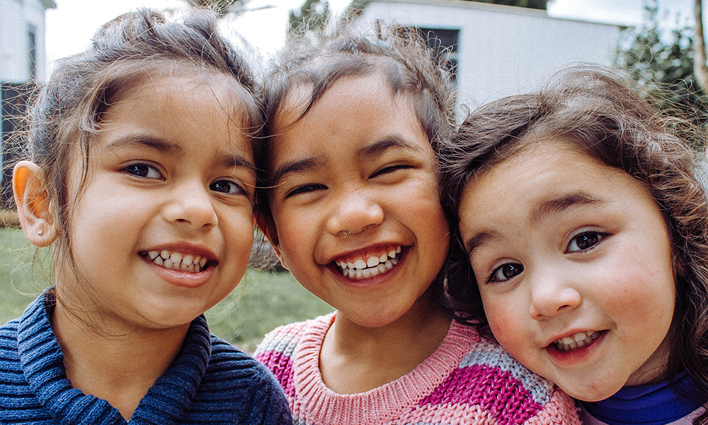 Closeup of three smiling girls with brown eyes and wavy brown hair