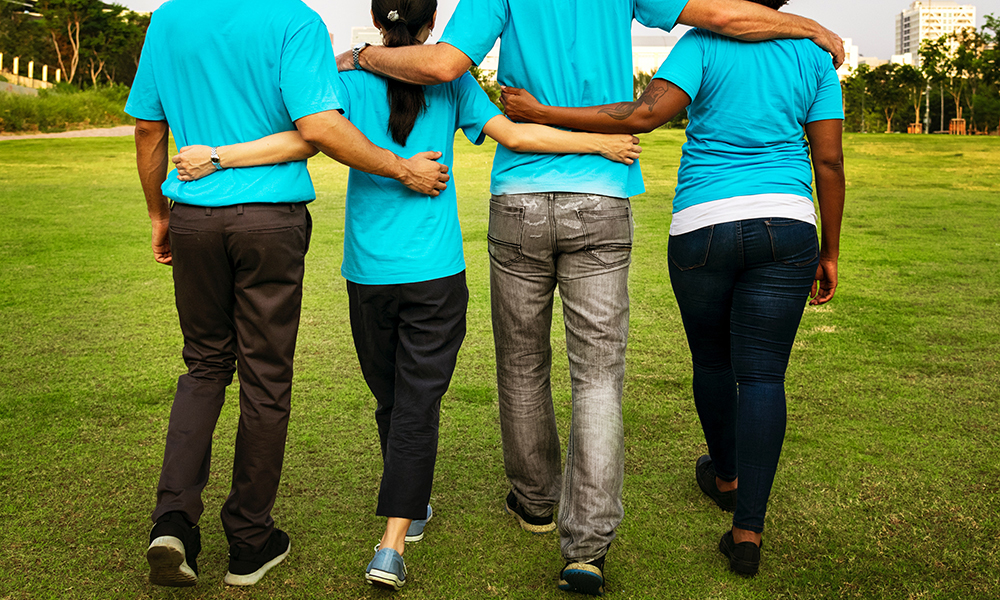 Two men and two women in matching light blue t-shirts walking away with their arms around each other
