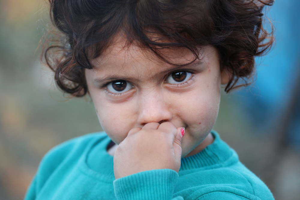 Closeup of female toddler with hand in mouth, very big brown eyes, short curly brown hair and turquoise sweatshirt
