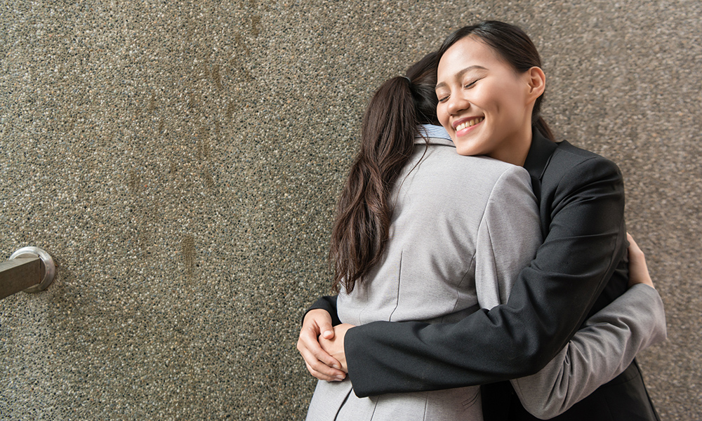 Smiling woman in black suit hugs woman in grey suit in front of concrete wall