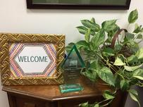 "A framed, hand made picture on a desk that says ""Welcome"", meant to represent the warmth and compassion clients seeking humanitarian protection and human rights protection will receive from Casa Cornelia Law Center."